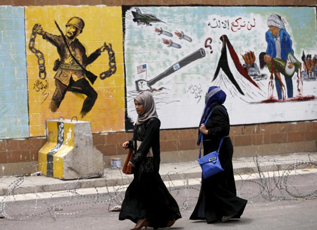 Women walk past graffiti painted by pro-Houthi activists on the wall of the Saudi embassy in Yemen's capital Sanaa August 18, 2015