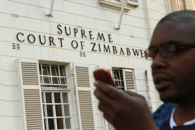 A journalist checks his mobile phone outside the Constitutional Court in Harare, 9 August 2013