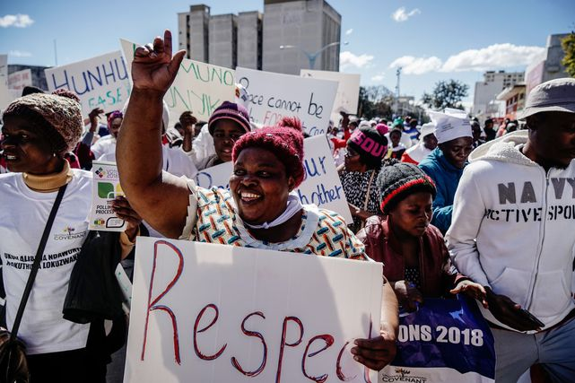A demonstrator holds a placard as she takes part in a march for peace ahead of national elections, Bulawayo, Zimbabwe, 2018